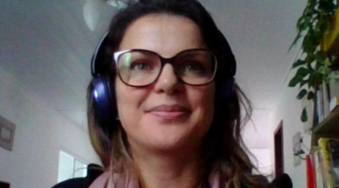 #Pracegover Foto: na imagem há uma muher de óculos e com fone de ouvido