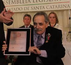 #Pracegover Foto: na imagem o ex-deputado Macari sendo homenageado na Alesc