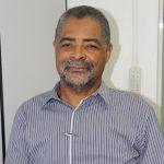 #Pracego ver Foto: na imagem há um homem com barba grisalha e camisa listrada