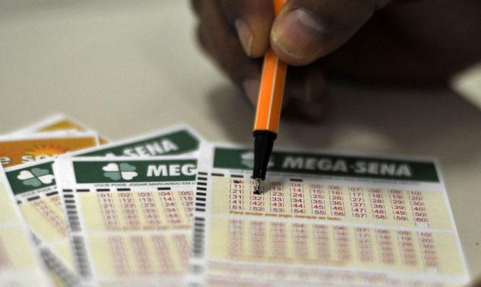 #Pracegover Foto: na imagem há alguns cartões da Mega-Sena e uma pessoa com uma caneta marcando os números