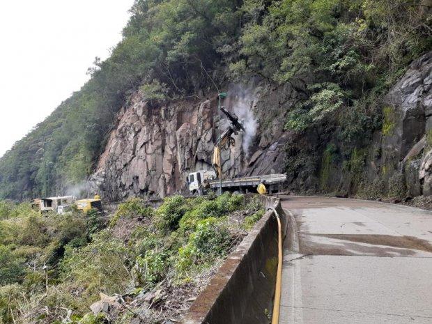 #Pracegover Foto: na imagem há um caminhão, pedras e árvores e folhas verdes