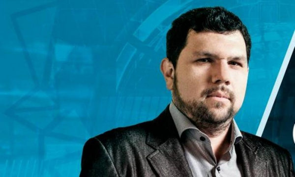 #Pracegover Foto: na imagem há um homem de terno preto e camisa cinza