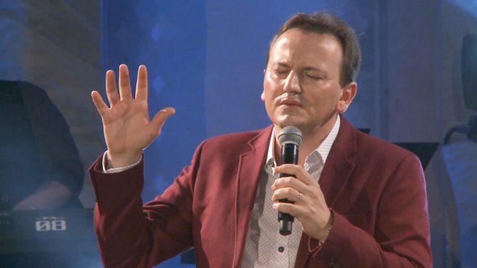 #Pracegover Foto: na imagem há um homem de terno, com uma mão levantada e a outra segurando um microfone