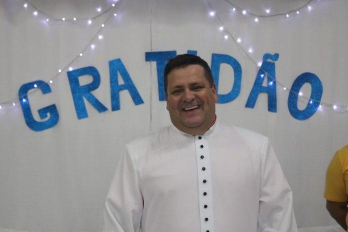 #Pracegover Foto: na imagem há um homem de roupa branca e atrás há uma mensagem de gratidão