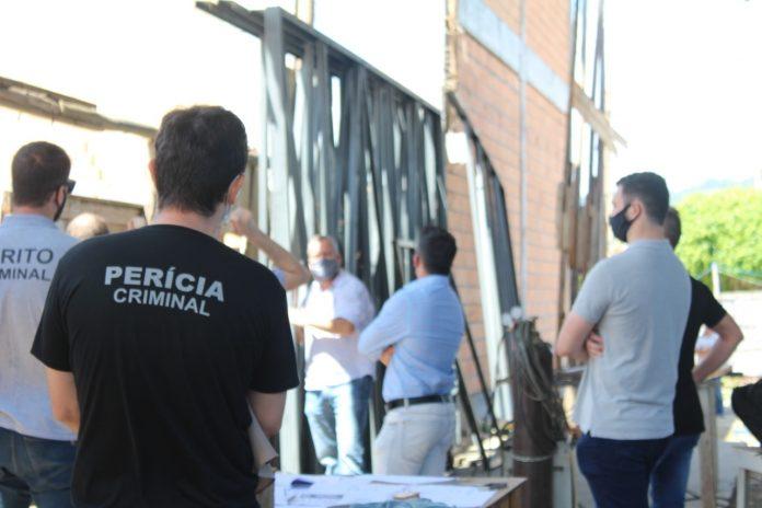 #Pracegover Foto: na imagem há alguns homens, um prédio em construção e materiais de construção