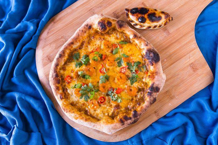 #Pracegover Foto: na imagem há uma pizza, uma tábua de carne e uma toaha de mesa na cor azul