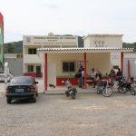 #Pracegover Foto: na imagem há duas edificações, motos e um carro