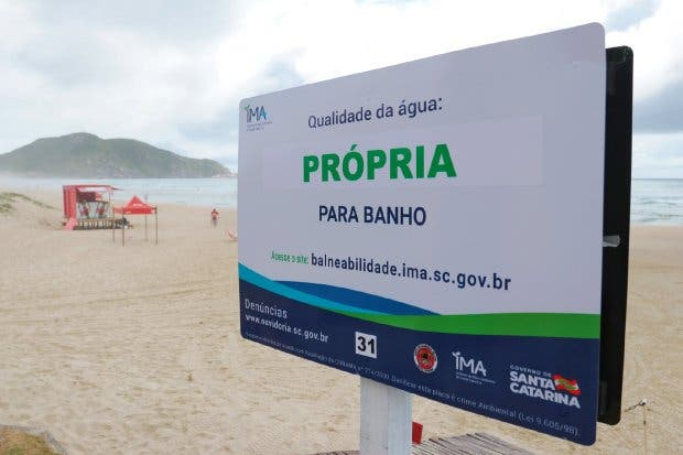 #Pracegover Foto: na imagem há uma placa, o mar e a areia da praia