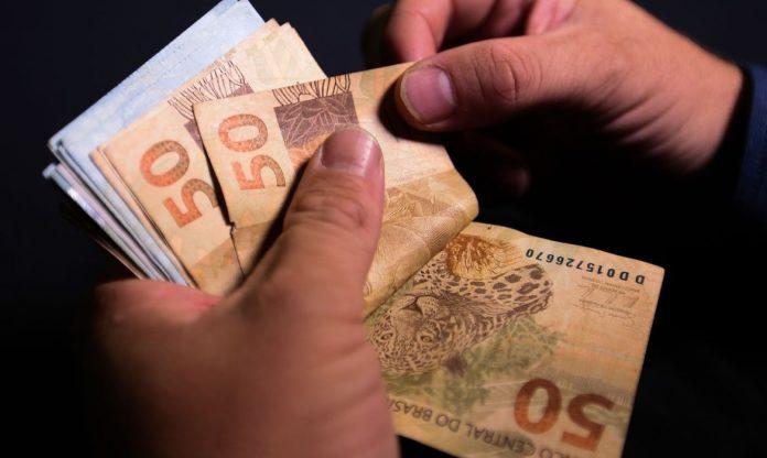 #Pracegover Foto: na imagem uma pessoa segura e conta o dinheiro