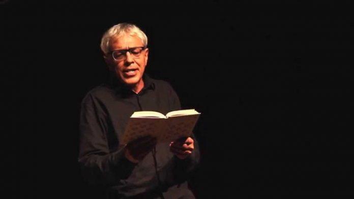 #Pracegover Foto: na imagem há um homem com cabelos grisalhos, roupa preta e um livro nas mãos