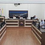 #Pracegover Foto: na imagem há vários homens, computadores e três mesas