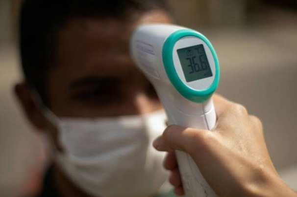 #Pracegover Foto: na imagem uma pessoa está com termômetro aferindo a temperatura de um jovem