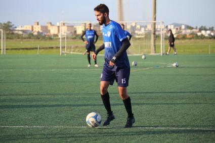 #Pracegover Foto: na imagem há um jogador treinando com bola em um campo. Outro atleta observa o colega e há várias bolas no campo