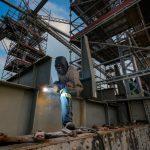 #Pracegover Foto: na imagem há um homem com uma máquina de soldagem e uma edificação