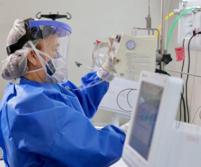 #Pracegover Foto: na imagem há uma profissional de saúde com EPI e aparelhos próprios de UTI
