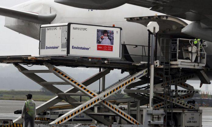 #Pracegover Foto: na imagem há um avião, ao lado uma estrutura metálica e um contêiner contendo vacinas