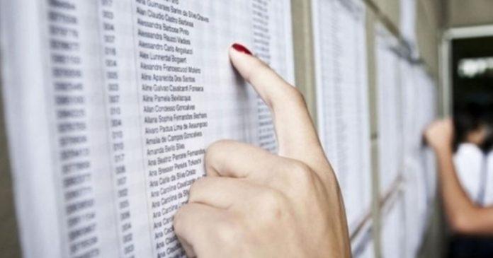 #Pracegover Foto: na imagem há a mão de uma mulher, que procura nomes em uma lista de aprovados de vestibular