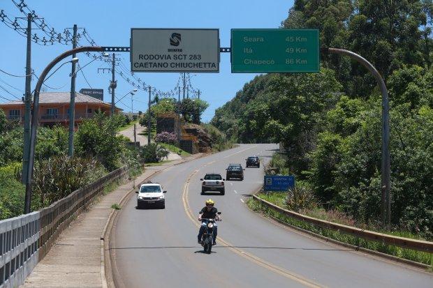 #Pracegover Foto: na imagem há uma rodovia com alguns carros, uma moto, algumas placas, árvores e uma casa