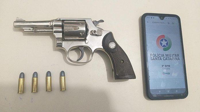#Pracegover Foto: na imagem há uma arma, quatro munições e um celular