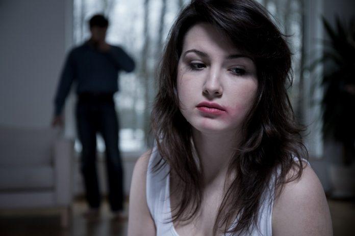 #Pracegover Foto: na imagem há uma mulher triste e um homem ao fundo