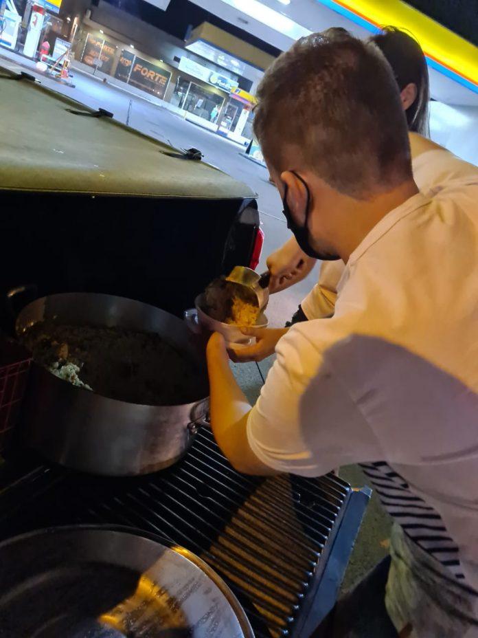 #Pracegover Foto: na imagem há um homem preparando o alimento e colocando em um recipiente. Há também uma mulher que segura esse recipiente e um carro