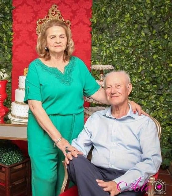 #Pracegover Foto: na imagem há um casal de idoso. Ele sentado e ela ao seu lado em pé