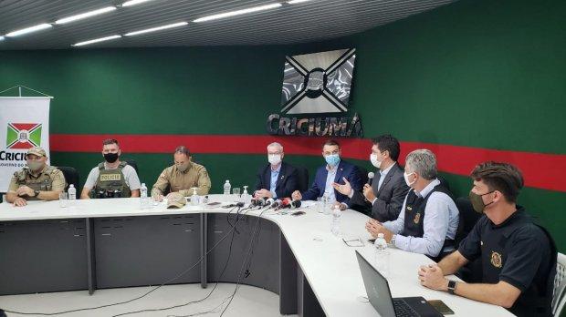 #Pracegover Foto: na imagem há vários homens que participam de uma coletiva de imprensa