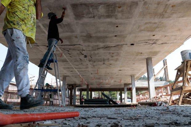 #Pracegover Foto: na imagem há três homens em uma obra de construção civil