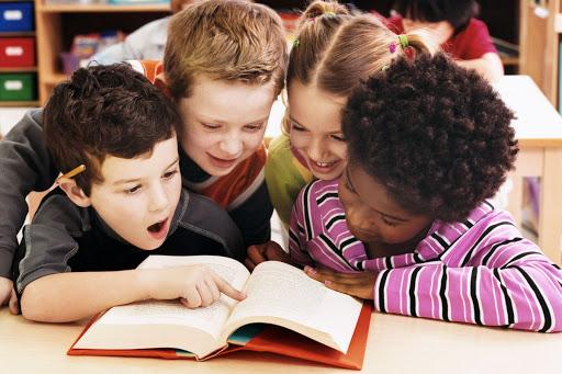 #Pracegover Foto: na imagem há quatro crianças em uma biblioteca lendo um livro