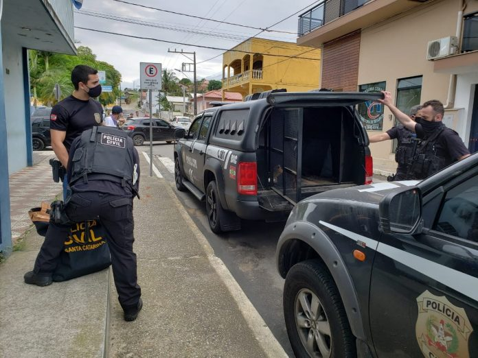 #Pracegover Foto: na imagem há policiais, viaturas e casas