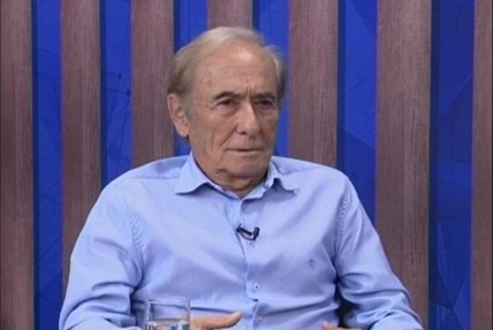 #Pracegover Foto: na imagem há um homem de camisa azul. Ele está sentado