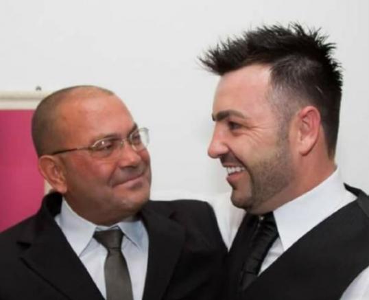 #Pracegover Foto: na imagem há dois homens de terno (pai e filho)