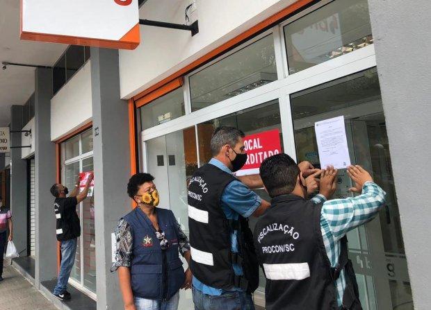 #Pracegover Foto: na imagm há três homens e uma mulher fiscalizando e fechando um estabelecimento