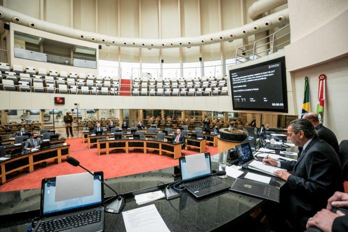 #Pracegover Foto: na imagem há o plenárioda Alesc com mesas, cadeiras, notebooks e algumas pessoas participam da sessão