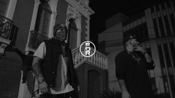 #Pracegover Foto: na imagem há duas pessoas com máscara e uma sem em uma foto escura. Além de um prédio histórico