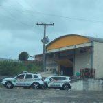 #Pracegover Foto: na imagem há um galpão, duas pessoas próximas a entrada do local, duas viaturas, um carro preto e estrados
