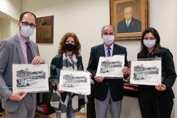 #Pracegover Foto: na imagem há quatro pessoas segurando imagens