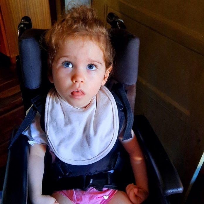 #Pracegover Foto: na imagem há uma criança, uma menina de 2 anos, com babador, blusinha azul e short rosa