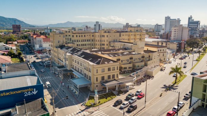 #Pracegover Foto: na imagem há o prédio do Hospital Nossa Senhora da Conceição, estacionamento, carros, edifícios, rua e avenida e pessoas