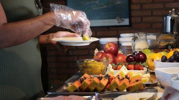 #Pracegover Foto: na imagem há muitas frutas, uma pessoa com luvas e um prato