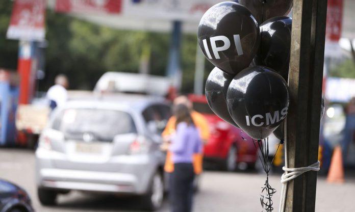 #Pracegover Foto: na imagem há carros, balões pretos, um poste e pessoas na rua