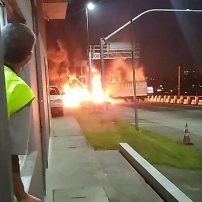 #Pracegover Foto: na imagem há um homem observando o fogo em um veículo