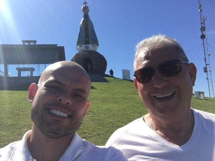 #Pracegover Foto: na imagem há dois homens sorridentes e no fundo há também há imagem de Nossa Senhora Aparecida