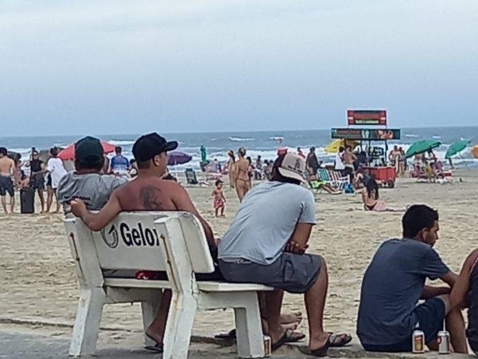 #Pracegover Foto: na imagem há o mar, areia e muitas pessoas aglomeradas