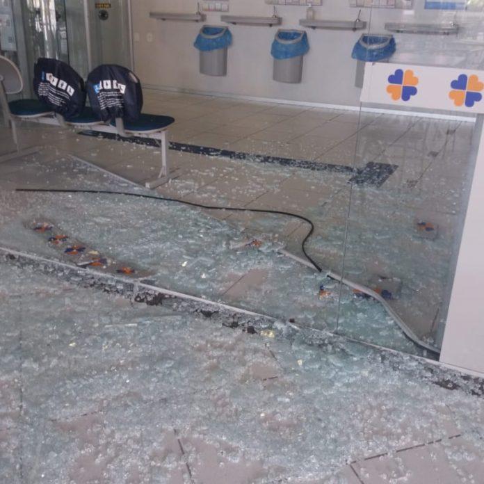 #Pracegover Foto: na imagem há uma agência lotérica com vidros quebrados, bancos e cestas de lixo