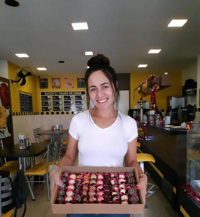 #Pracegover Foto: na imagem há uma mulher com uma caixa de doces. Ela está em um estabelecimento comercial