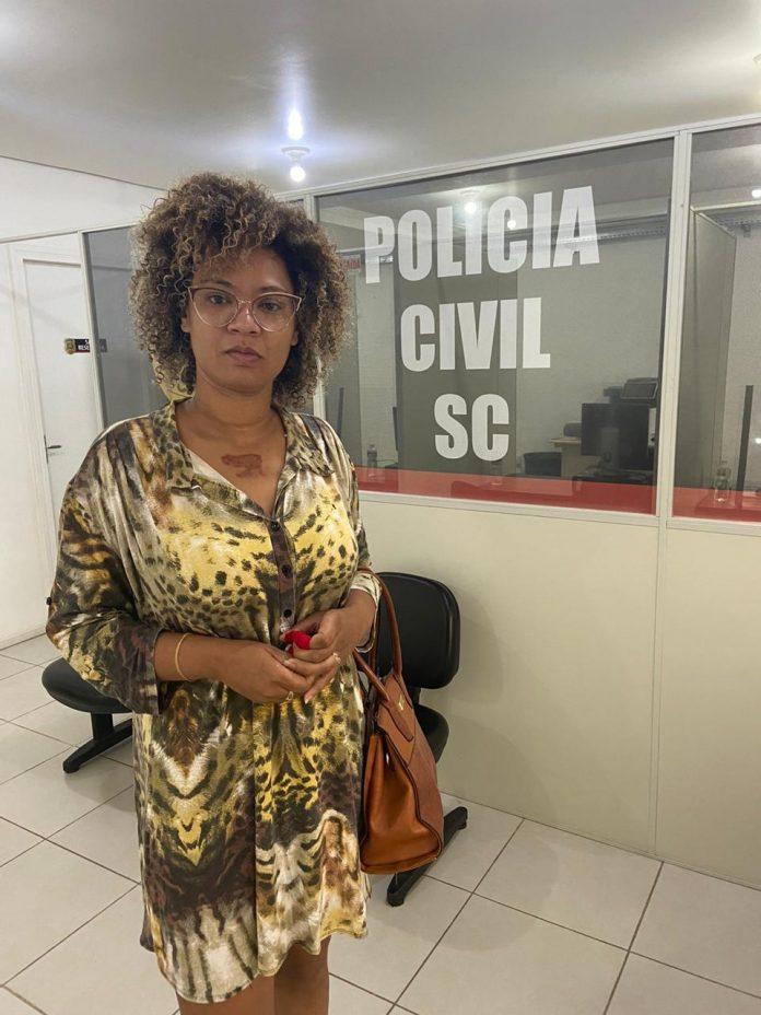 #Pracegover Foto: na imagem há uma mulher de vestido, de óculos e com uma bolsa