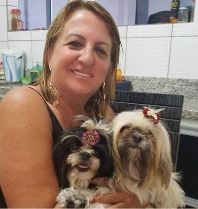 #Pracegover Foto: na imagem há uma mulher sorridente. Ela está com duas cachorrinhas no colo