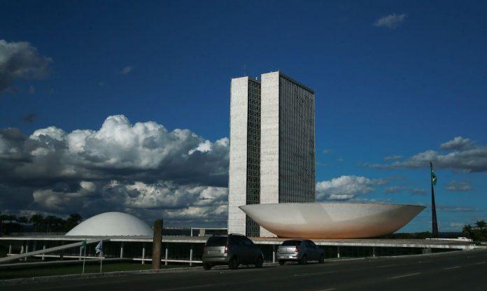 #Pracegover Foto: na imagem há dois carros e monumentos do congresso