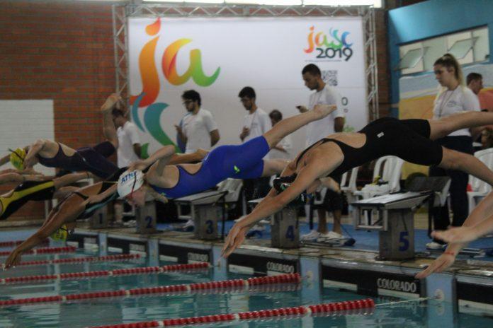 #Pracegover Foto: na imagem há várias pessoas e algumas delas se jogam na piscina